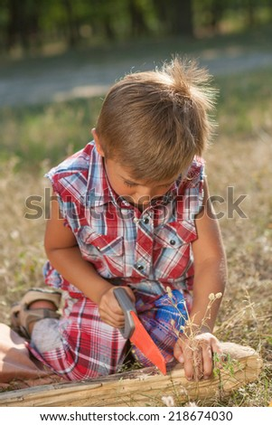 Little boy with toy hand tools drill and saw. Emotional, hard at work outside.