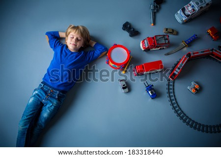Little boy with toys in studio - stock photo