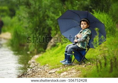 little boy with umbrella - stock photo