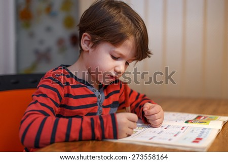 Little boy write maths exercise at home - stock photo