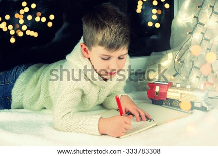 Little boy writes letter to Santa.