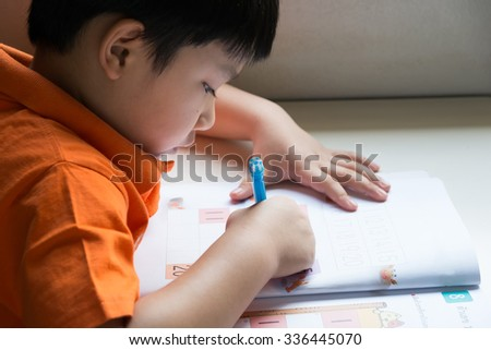 Little Boy Writing Math Exercise At Home