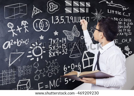 Little boy writing mathematics formula on the chalkboard while holding a book in the classroom