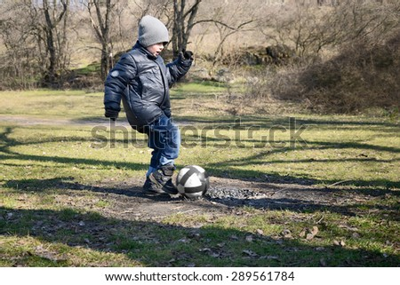 little boy 6-7 years hits the ball to score a goal. outdoor, side view