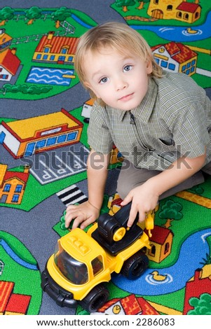 Little boy (2,5 years old) sitting on the floor and playing with his toy. - stock photo