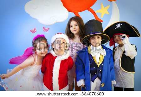 Little boys and girls in costumes in a school play or ready for halloween enjoying the day against blue background. - stock photo