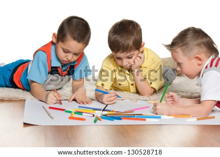 Little boys are lying on the floor and drawing on paper - stock photo