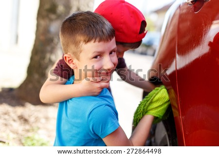 Little boys cleaning splash guard, outdoor car wash - stock photo