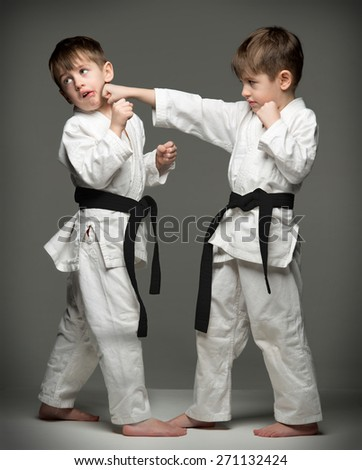 Little boys in uniform practicing judo. The same person two times - stock photo