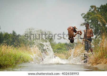 little boys jumping and playing in the irrigation canal,countryside thailand.
