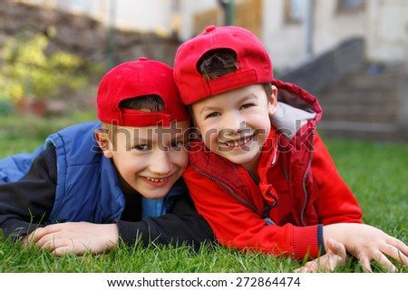 Little boys laughing in grass at backyard - stock photo