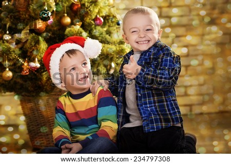 Little boys near a Christmas tree. Children in cap of Santa - stock photo