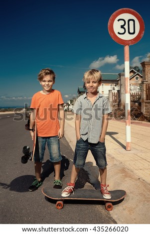 Little boys on longboard skate