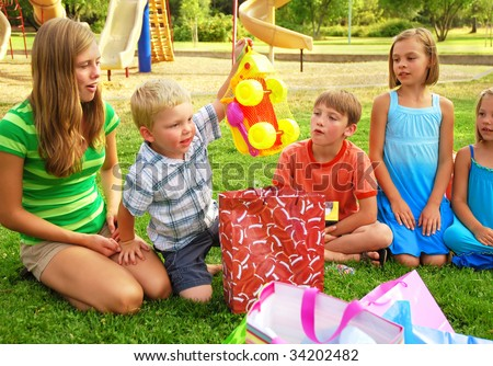 Little boys opening gifts at his birthday party - stock photo