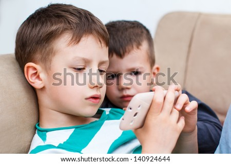 Little boys playing on smartphone - stock photo