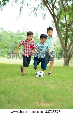 Little boys playing soccer in the park - stock photo