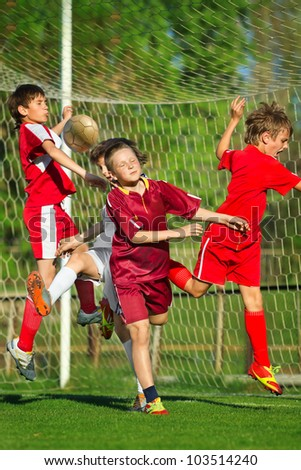 Little Boys playing soccer on the sports field next to goal - stock photo