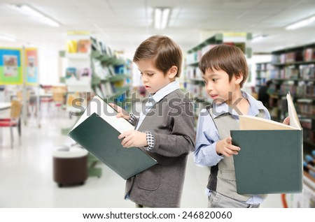 Little boys reading books in the library - stock photo