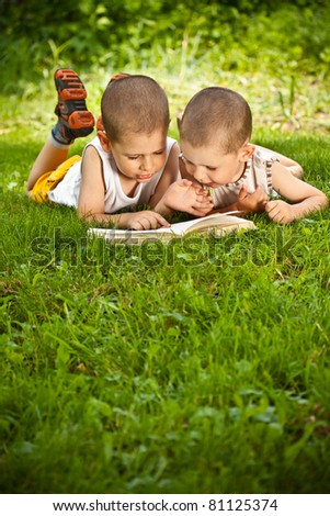 little boys reads a book in green grass - stock photo