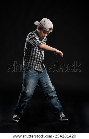 little break dancer showing his skills on black background. Hip hop dancer boy performing isolated over dark background  - stock photo