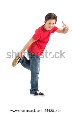 little break dancer showing his skills on grey background. Hip hop dancer boy performing isolated over dark background - stock photo