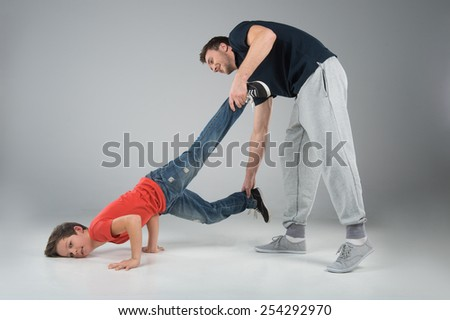 little break dancer showing his skills on grey background. man helping dancer boy performing isolated over dark background  - stock photo