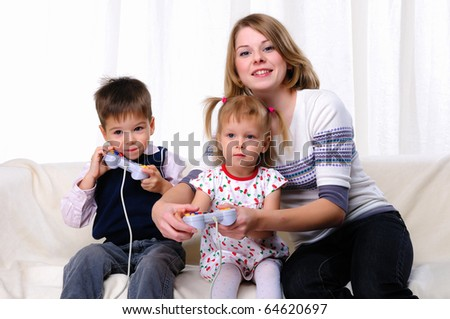 Little brother and sister and his mother played video games while sitting on the couch - stock photo
