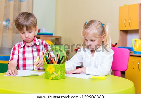 Little brother and sister drawing at home - stock photo
