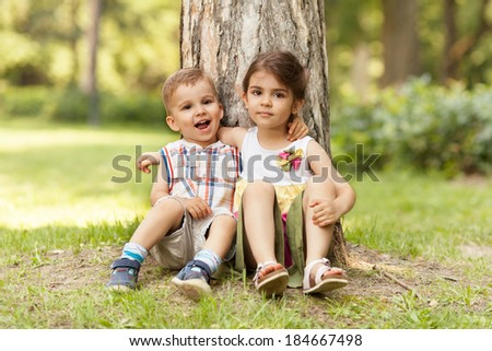 Little brother and sister expressing affection, sitting in nature and hugging.