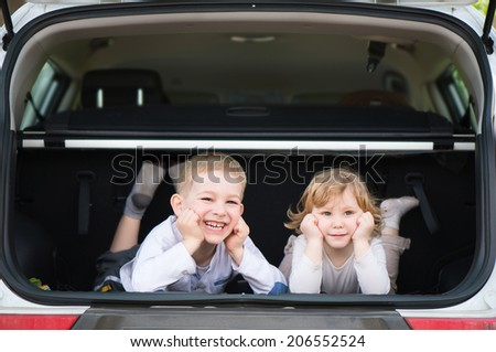 Little brother and sister in car boot during summer vacation - stock photo