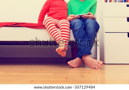 little brother and sister looking at mobile phone, focus on feet