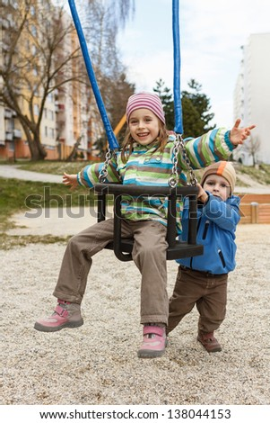 Little brother and sister playing on the swing on the playground