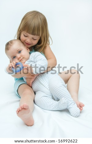 little brother and sister playing together, on white - stock photo