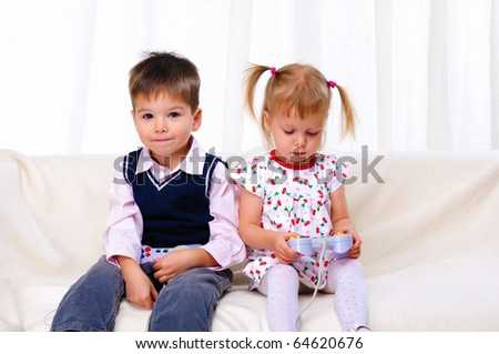 Little brother and sister playing video games lying on the couch - stock photo