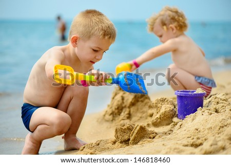 Little brother and sister playing with sand at ocean beach - stock photo