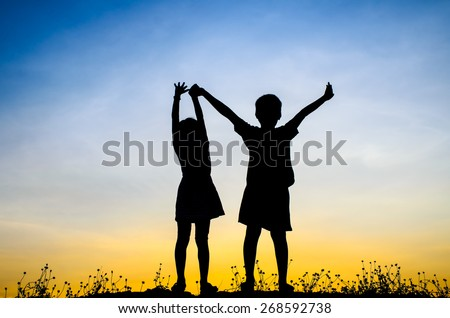 Little brother and sister silhouette - stock photo