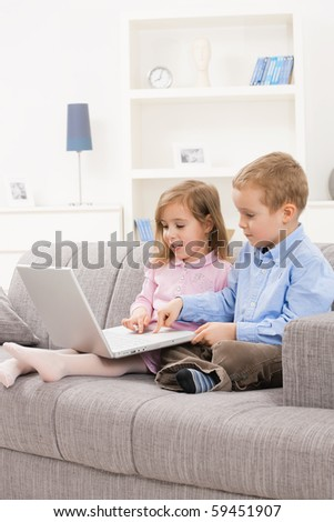 Little brother and sister sitting together on couch at home, using laptop computer, looking at screen. - stock photo