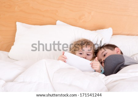 Little brother and sister snuggling up together at bedtime under a warm duvet as they read an e-book or surf the internet on a tablet-pc - stock photo