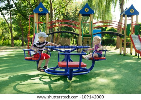 Little brother and sister spinning on roundabout at playground - stock photo