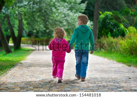 Little brother and sister walking by footpath at summer park - stock photo