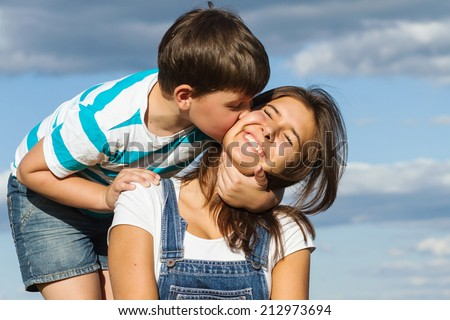 Little brother hugging and kissing his older sister's cheek against the blue sky - stock photo