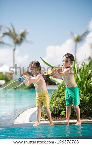 Little brothers playing with water toy in the swimming pool - stock photo