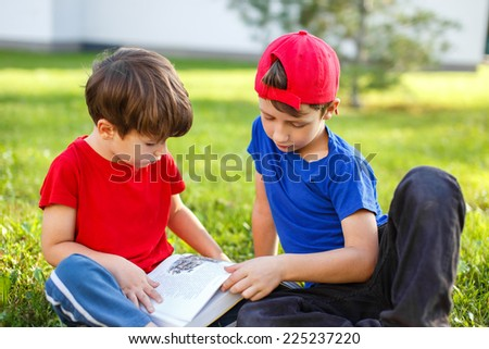 Little brothers reading book in nature, education - stock photo
