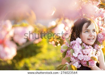 Little brunette girl looking away standing amid pink japanese cherry flowering in broad daylight in the park copyspace, horizontal picture - stock photo