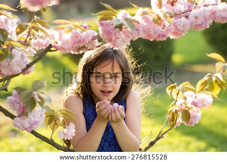 Little brunette girl looking forward smelling cherry bloom standing among pink japanese cherry blossom in broad daylight in the park, horizontal picture - stock photo