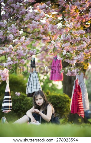 Little brunette girl with basket looking forward sitting in the garden among colorful baby dresses hanging in the japanese cherry blossom tree, vertical picture - stock photo
