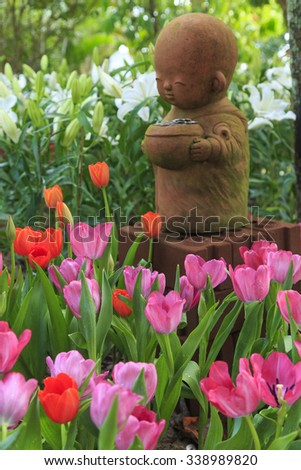 Little Buddha statue with pink tulip in the garden - stock photo