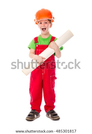 Little builder standing in red overalls and hard hat with paper plan in hands, isolated on white