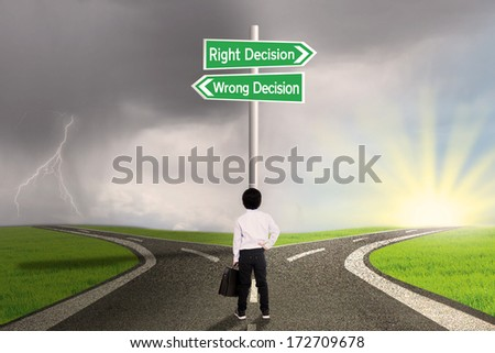 Little business child is standing on the road with a sign of right vs wrong decision - stock photo