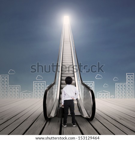 Little businessman at escalator with cityscape - stock photo
